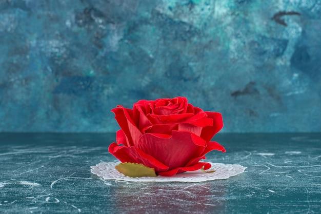 Rose rouge sur un sous-verre, sur fond bleu.