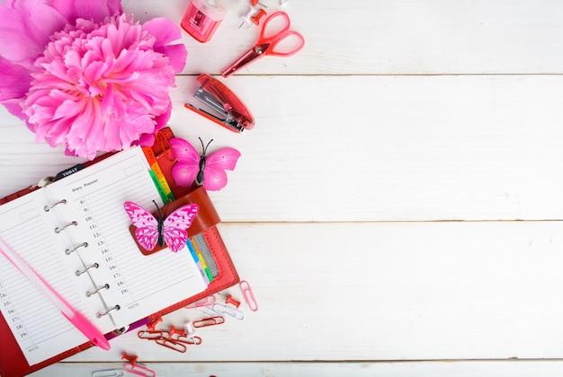 Rose et rouge stationnaire avec fleur sur fond de table en bois blanc