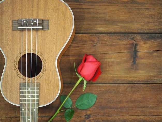 Rose rouge et ukulélé sur fond en bois pour la carte de la saint-valentin.