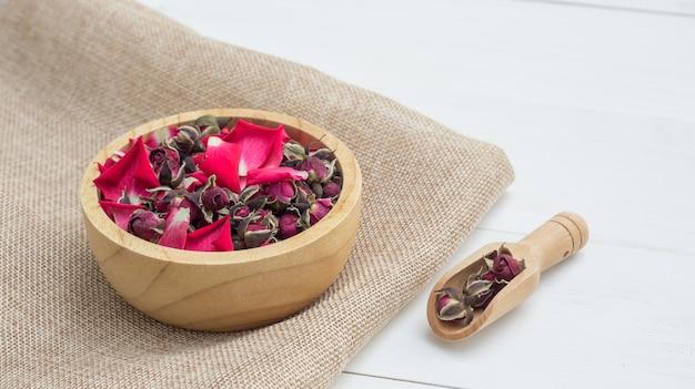 Une rose sèche de thé rose sur une table en bois blanche.