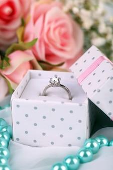 Roses et un anneau sur un tissu blanc