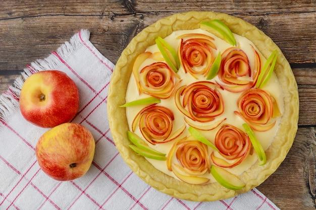Roses aux pommes rouges et garniture à la crème dans une tarte à la croûte.