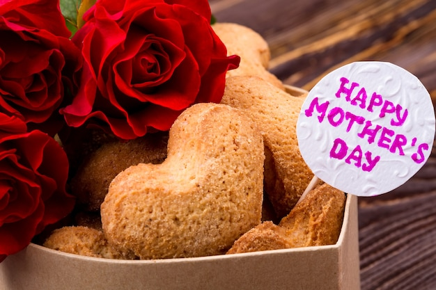 Roses et biscuits. carte de voeux sur boîte à biscuits. dessert maison pour maman. la manière la plus mignonne de féliciter.