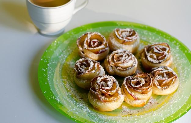 Roses de biscuits faits maison avec une poudre de sucre sur une assiette colorée et une tasse de café au lait. concept de petit déjeuner et dessert.