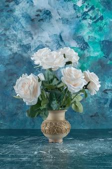 Roses blanches artificielles dans un vase, sur fond bleu.
