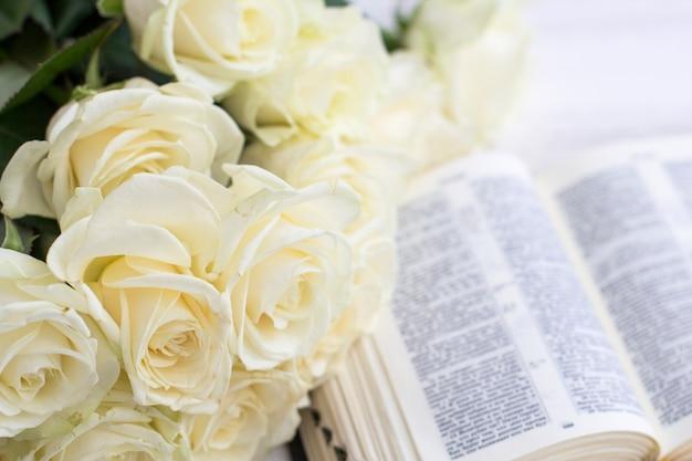 Les roses blanches et la bible. roses blanches et la bible sur un fond en bois blanc