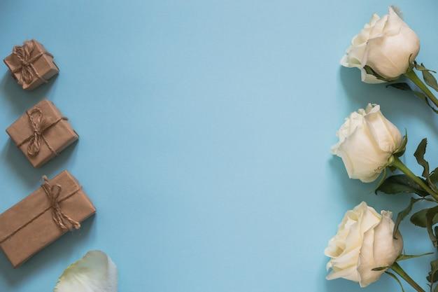 Roses blanches et cadeaux de papier craft sur fond bleu. joyeuse saint-valentin ou fête des mères.