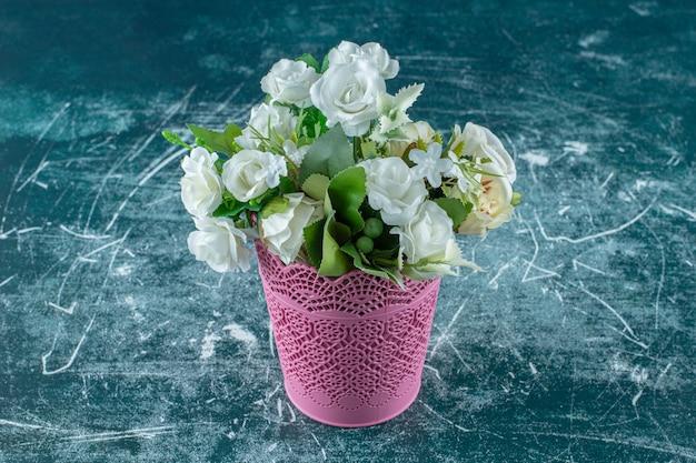 Roses blanches dans un pot de fleurs rose, sur fond blanc. photo de haute qualité