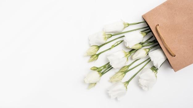 Roses blanches dans un sac cadeau en papier vue de dessus