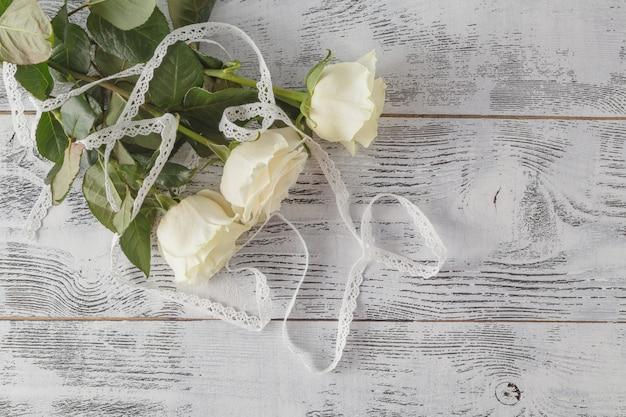 Roses blanches sur fond en bois. mise au point sélective, espace de copie