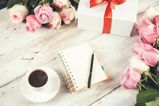 Roses avec cadeau et bloc-notes avec tasse de café sur la table