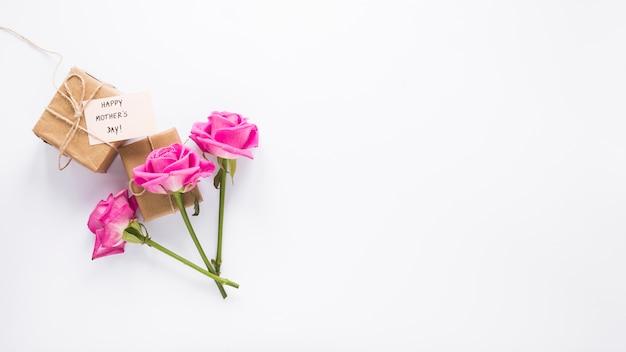 Roses avec des cadeaux et inscription heureuse fête des mères