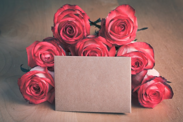 Roses et carte d'artisanat vierge sur la table