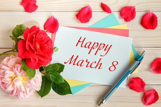 Des roses et une carte avec l'inscription - happy march 8. journée internationale de la femme