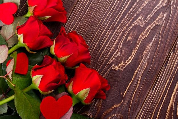 Roses et coeurs sur bois. fleurs fraîches de couleur rouge. impressionnez votre fille bien-aimée. vacances d'amour et de joie.