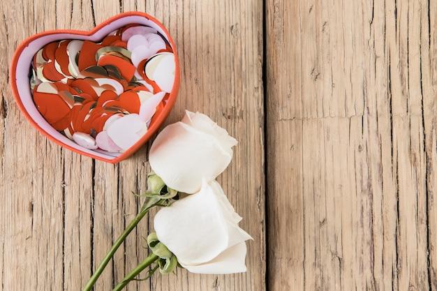 Roses avec des coeurs de papier dans une boîte
