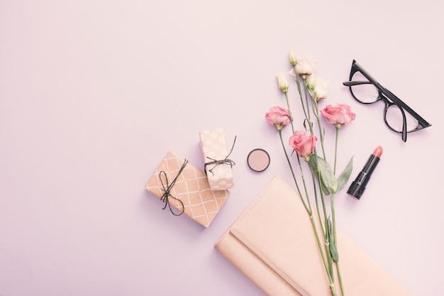 Roses avec des coffrets cadeaux et du rouge à lèvres sur la table
