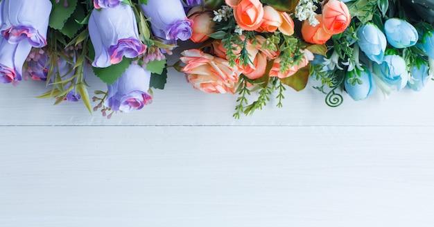 Roses colorées avec des branches sur fond de bois blanc, mise à plat.
