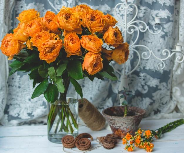 Roses de couleur orange dans un pot avec de l'eau