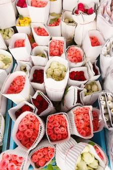Roses de couleurs vives enveloppées dans du papier blanc