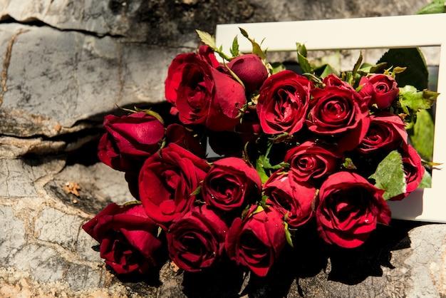Roses dans un cadre blanc sur la pierre. fond du concept de jour de la saint-valentin et le concept de l'amour.