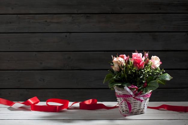 Roses dans un panier avec fond en bois de ruban