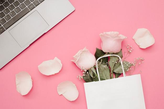 Roses dans le sac à provisions et ordinateur portable sur fond rose