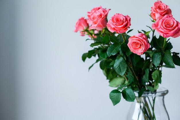 Roses dans un vase transparent sur un fond gris avec un espace pour votre texte.