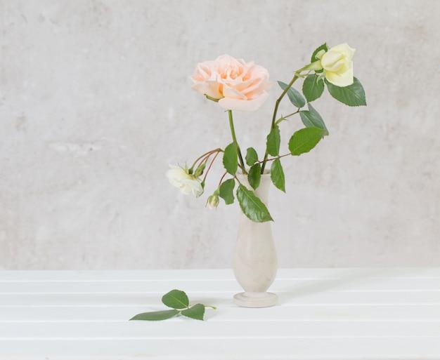 Roses dans un vase sur vieux blanc