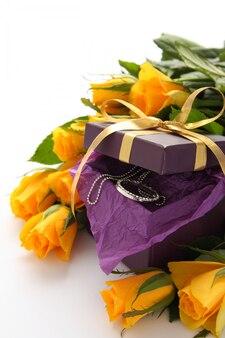 Roses jaunes et coffret violet avec des bijoux sur fond blanc
