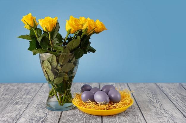 Roses jaunes dans un vase à côté d'une plaque jaune avec des oeufs de pâques bleus