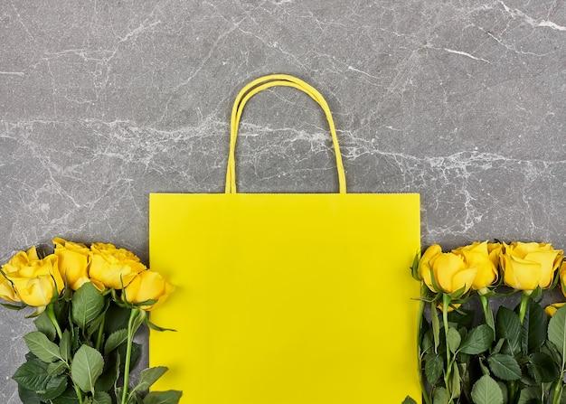 Roses jaunes, sac en papier jaune sur fond gris