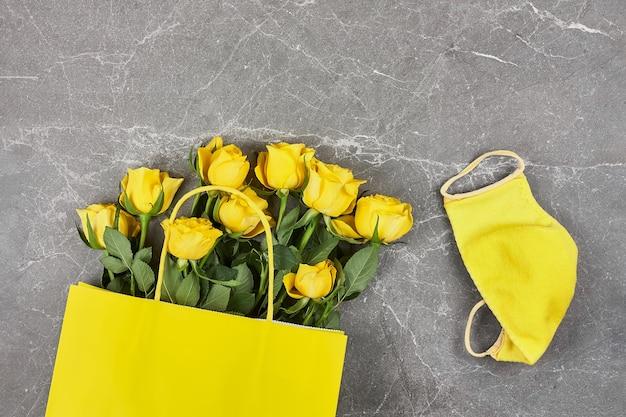 Roses jaunes, sac en papier jaune, masque de protection jaune sur fond gris