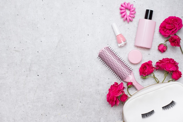 Roses lumineuses rouges et accessoires de maquillage portant sur un fond gris clair