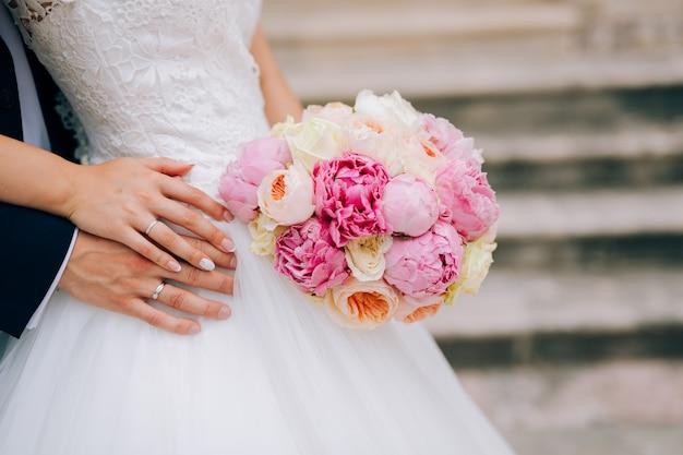 Roses de mariage et pivoines entre les mains de la mariée