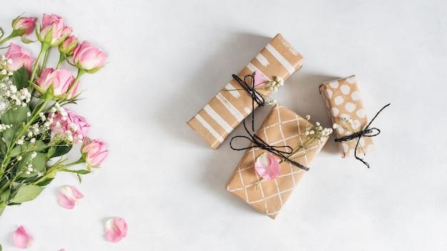 Roses merveilleuses fraîches près des boîtes de cadeau et des pétales