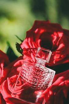Roses de parfum et parfumerie de lumière du soleil comme fond de flatlay de beauté de cadeau de luxe et annonce de produit cosmétique