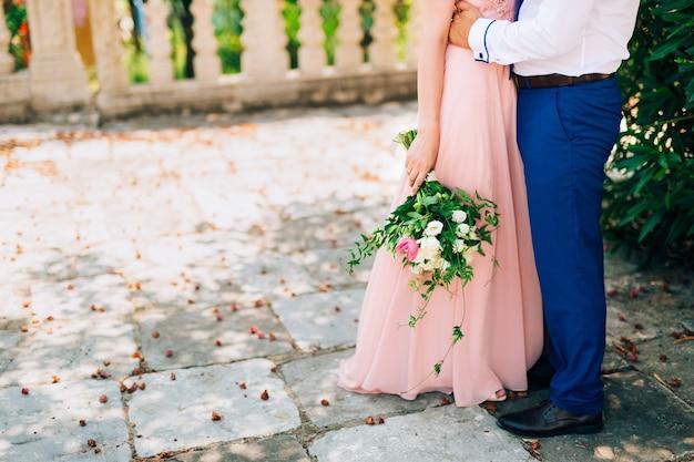 Roses et pivoines de mariage dans les mains du mariage de la mariée