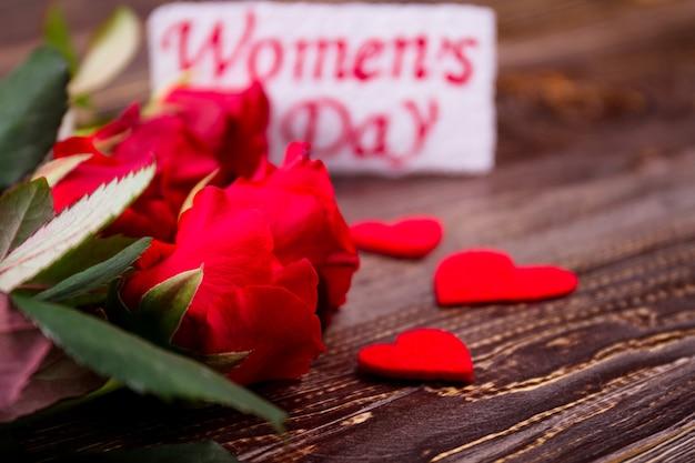 Roses près de la carte de la journée de la femme. coeurs et fleurs. complétez votre cadeau avec bloom. pétales de joie.