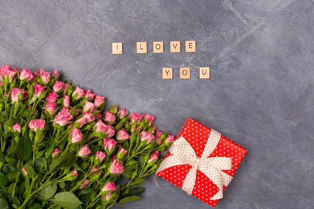 Roses roses en aérosol, cadeau dans une boîte rouge et je t'aime sur fond gris. concept de la saint-valentin de la mère de la femme
