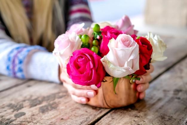 Roses roses et blanches dans un plat en cuivre dans les mains de la femme sur une table en bois texturé dans un café en plein air. concept de mode de vie.