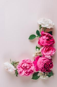 Roses roses et blanches sur fond beige vue de dessus cadre plat ou couronne