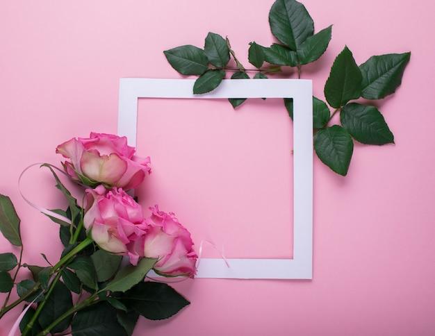 Des roses roses et un cadre en papier blanc sont décorés de feuilles fraîches sur fond rose