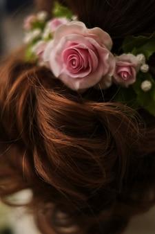 Roses roses dans les cheveux de la mariée, style de mariage, gros plan