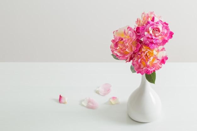 Roses roses dans un vase sur fond blanc