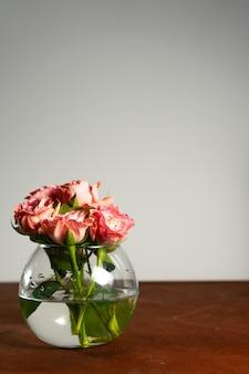 Roses roses dans un vase rond transparent sur une table en bois