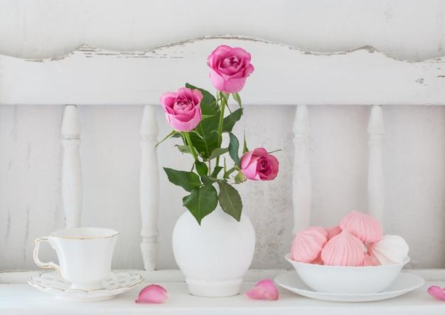 Roses roses dans un vase et de la vaisselle sur une étagère en bois blanc