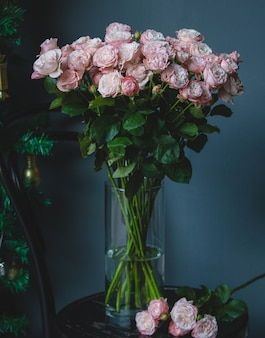 Roses roses dans un vase en verre avec de l'eau