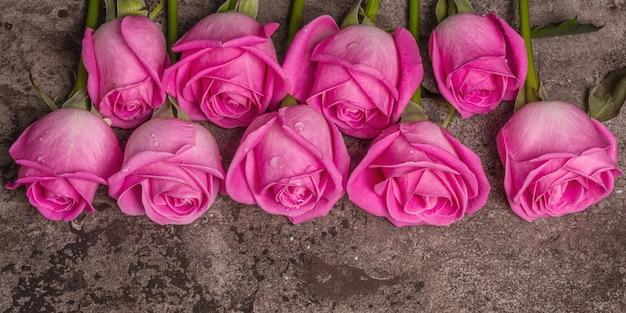 Roses roses fraîches sur fond de béton texturé en pierre. carte de voeux pour mariages, anniversaires, 8 mars, fête des mères ou saint-valentin, bannière