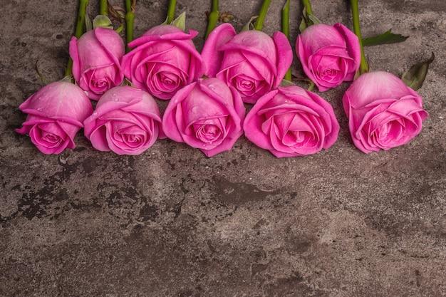 Roses roses fraîches sur fond de béton texturé en pierre. carte de voeux pour les mariages, les anniversaires, le 8 mars, la fête des mères ou la saint-valentin